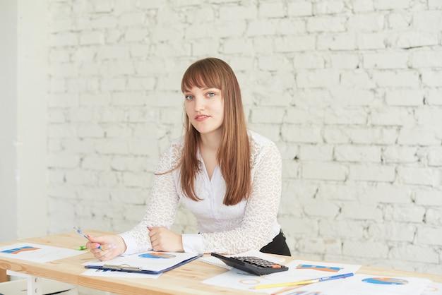 Schöne junge frau in eleganter freizeitkleidung, die diagramm beim stehen im büro betrachtet.