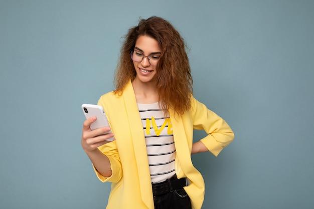 Schöne junge frau in freizeitkleidung, die isoliert über dem hintergrund steht und per telefon im internet surft und auf den mobilen bildschirm schaut.