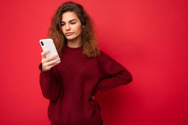 Schöne junge frau in freizeitkleidung, die isoliert über dem hintergrund steht und per telefon im internet surft und auf den mobilen bildschirm schaut