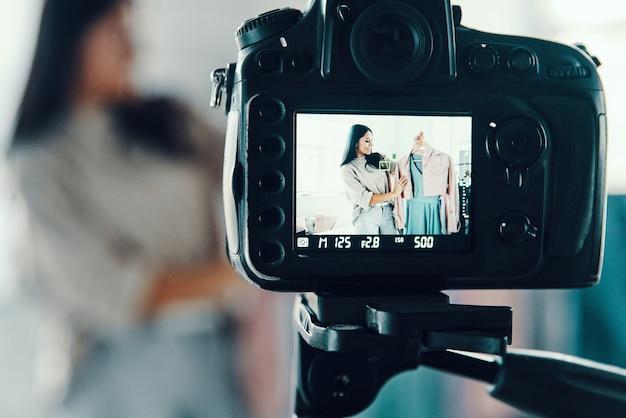 Schöne junge frau in freizeitkleidung, die social-media-videos macht, während sie zeit zu hause verbringt