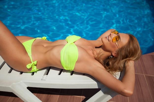 Schöne junge frau in gelben gläsern und in einem gelben badeanzug, der sich im sommer am pool sonnen