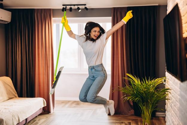 Schöne junge frau in gelben handschuhen, die mit mopp tanzt, während sie das wohnzimmer säubert.