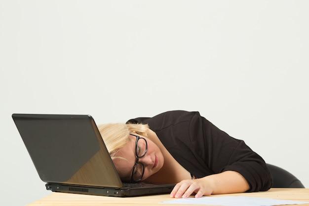 Schöne junge frau in gläsern am tisch mit einem laptop