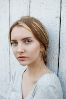 Schöne junge frau in grauer bluse, porträt im freien des netten durchdachten modells