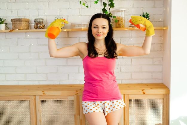 Schöne junge frau in gummihandschuhen putzt die küche zu hause