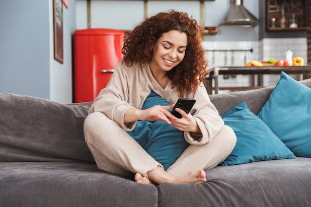Schöne junge frau in hauskleidung, die auf dem sofa in der wohnung sitzt und das handy benutzt