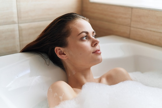Schöne junge frau in ihrer schönen schneeweißen badewanne ruht und entspannt, schöne beweise, badewanne mit schaum