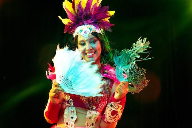 Schöne junge frau in karnevalsmaske und maskenkostüm in bunten lichtern