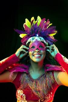 Schöne junge frau in karnevalsmaske und maskeradenkostüm in bunten lichtern
