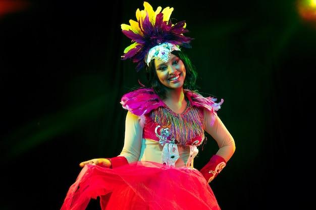 Schöne junge frau in karnevalsmaske und stilvollem maskenkostüm mit federn in bunten lichtern und leuchten an schwarzer wand