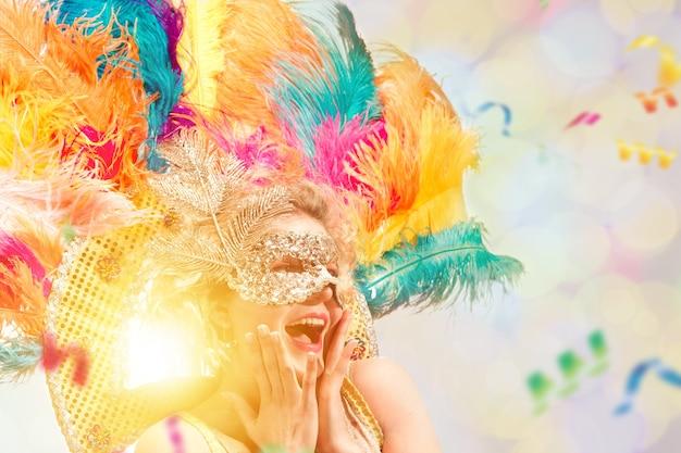 Schöne junge frau in karnevalsmaske