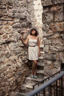 Schöne junge frau in kleid und hut, die an der alten steinburg spazieren geht