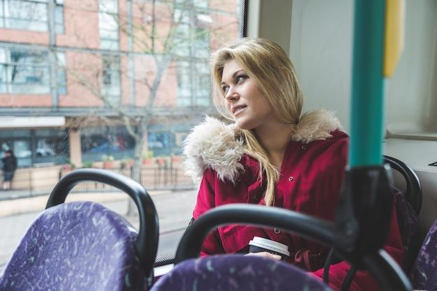 Schöne junge frau in london auf doppeldeckerbus