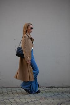 Schöne junge frau in modischen kleidern auf einem spaziergang in der herbststadt