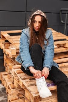 Schöne junge frau in modischer jeansjacke in jeans in lederstiefeln posiert auf den brettern auf der straße. stilvolles mädchenmodemodell, das auf holzpaletten in der stadt ruht. lässiger jugendstil.