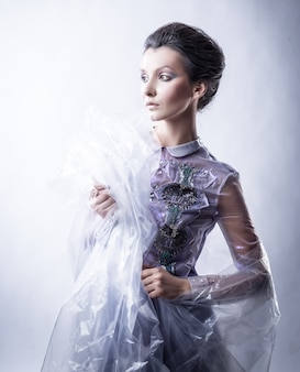 Schöne junge frau in modischer kleidung und transparentem cape