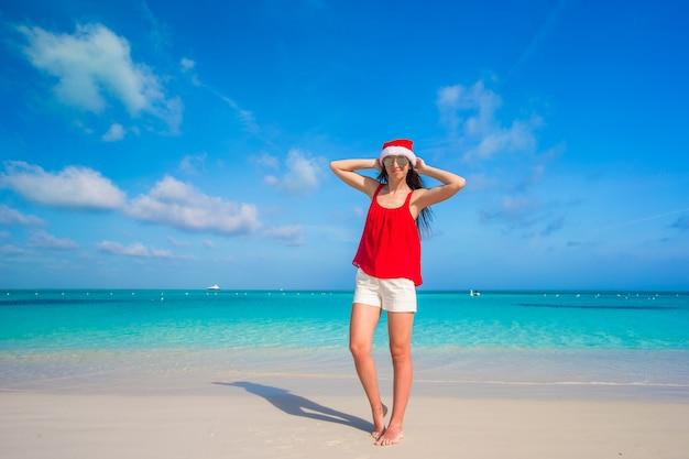 Schöne junge frau in nikolausmütze am tropischen strand