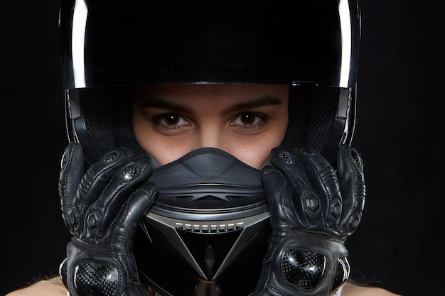 Schöne junge frau in schwarzen lederhandschuhen und schützendem motorradhelm. attraktive selbstbestimmte motorradrennfahrerin, die hände und körper vor stürzen und unfällen schützt