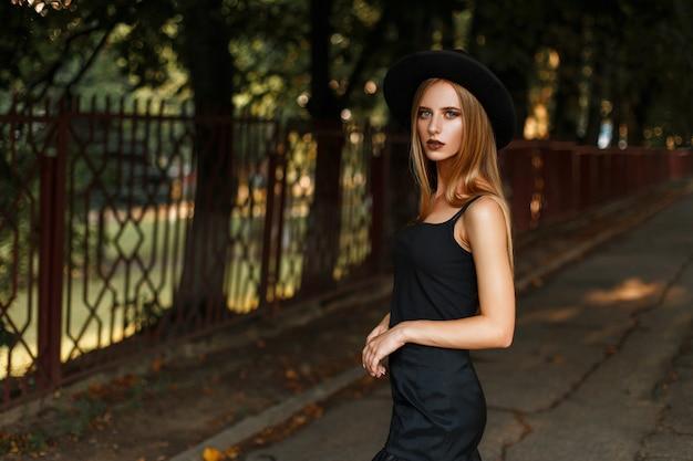 Schöne junge frau in schwarzen stilvollen kleidern und einem modischen hut