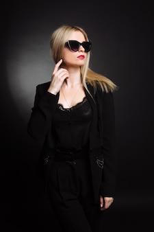 Schöne junge frau in schwarzer jacke und sonnenbrille auf schwarzem hintergrund. hübsches blondes mädchen