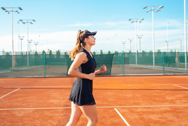 Schöne junge frau in schwarzer sportkleidung läuft auf dem tennisplatz herum