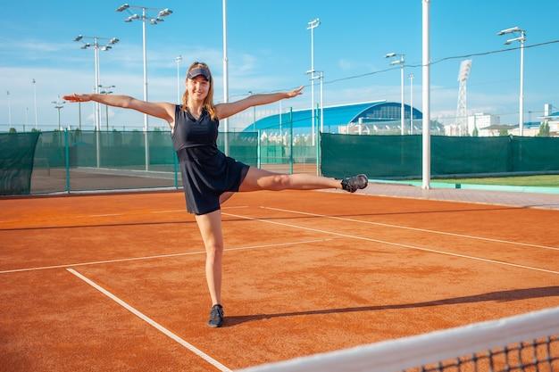 Schöne junge frau in schwarzer sportkleidung streckt sich im tennisplatz aus