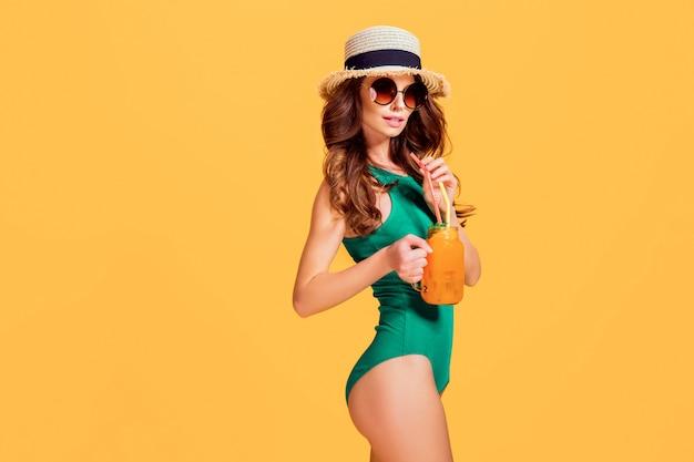 Schöne junge frau in smaragdgrüner badebekleidung und strohhut, die krug mit kaltem getränk hält