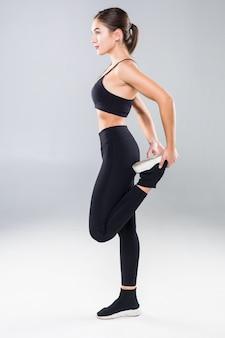 Schöne junge frau in sport stehende stretchmuskelbeinübung mit gesundem lokalisiert auf weißer wand