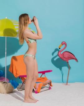 Schöne junge frau in trinkendem getränk des bikinis im studio
