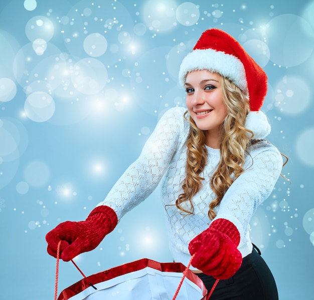 Schöne junge frau in weihnachtsmann-kleidung mit einem geschenk auf blauem hintergrund