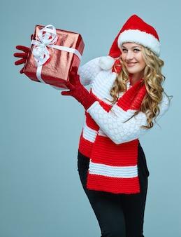 Schöne junge frau in weihnachtsmann-kleidung mit einem geschenk auf einem grau