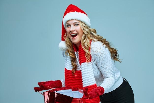 Schöne junge frau in weihnachtsmann-kleidung mit einem geschenk auf grauem hintergrund