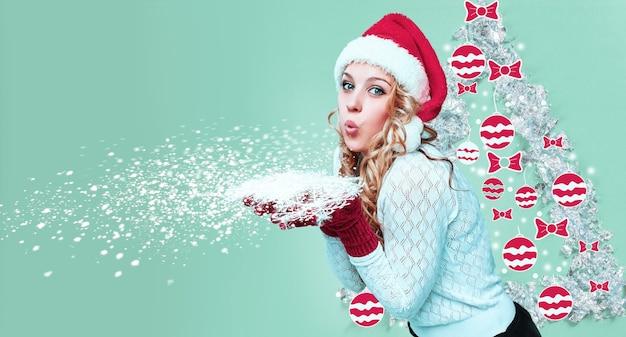 Schöne junge frau in weihnachtsmann-kleidung mit schneeflocken