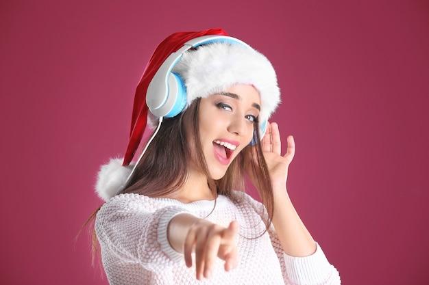 Schöne junge frau in weihnachtsmütze, die weihnachtsmusik auf farbigem hintergrund hört