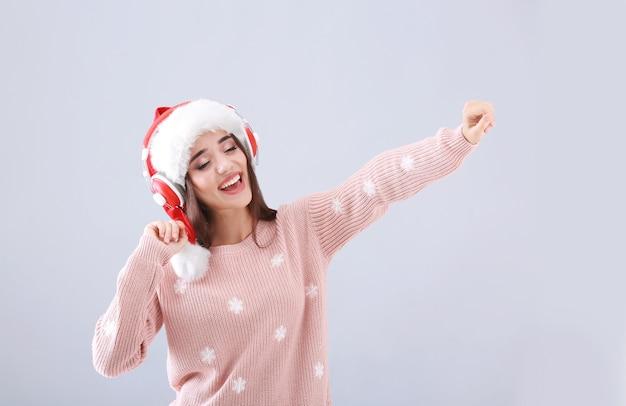Schöne junge frau in weihnachtsmütze, die weihnachtsmusik auf hellem hintergrund hört