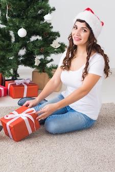 Schöne junge frau in weihnachtsmütze mit geschenken in der nähe von weihnachtsbaum zu hause.