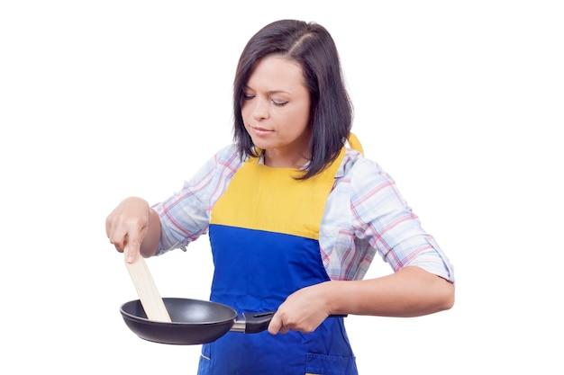 Schöne junge frau kocht essen mit bratpfanne auf weißem hintergrund