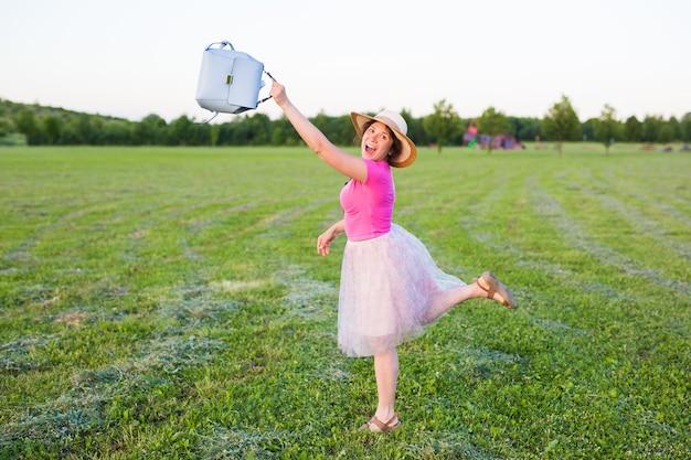 Schöne junge frau lacht und tanzt draußen auf einer wiese bei sonnenuntergang