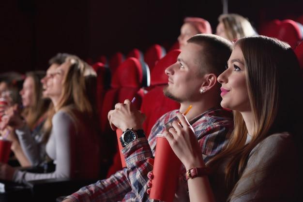 Schöne junge frau lächelnd sitzt neben ihrem freund im kino. liebevolles paar, das zusammen einen film sieht paare, die menschen freundschaft freizeit unterhalten.