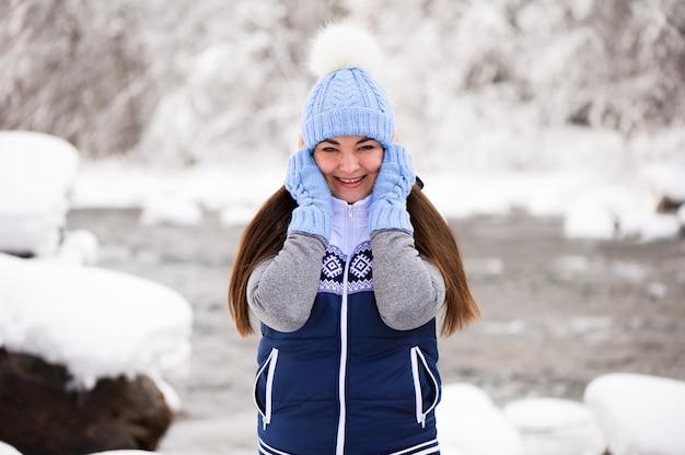 Schöne junge frau lächelnd und spielend mit schnee in der wintersaison