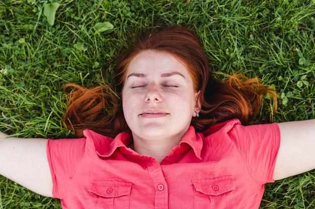 Schöne junge frau liegt im gras. frisches natürliches sommerkonzept. ausblick von oben.