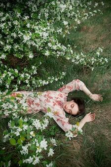 Schöne junge frau liegt im gras unter blühendem apfelbaum. romantisches mädchen ruht in der natur. frühlingsporträt der frau