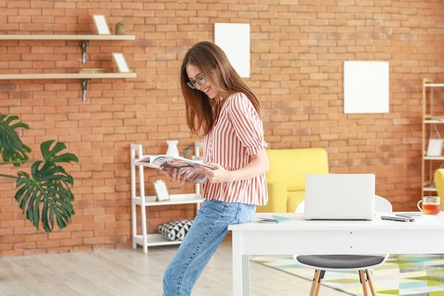Schöne junge frau liest zeitschrift im büro