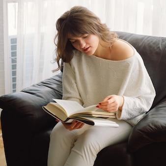 Schöne junge frau liest zu hause ein buch