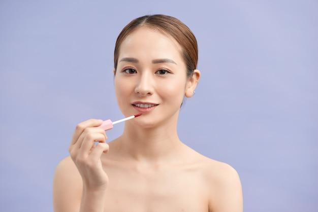 Schöne junge frau lipgloss auftragen. perfektes make-up. schöne lippen