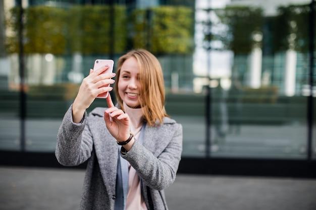 Schöne junge frau macht selfie-foto mit smartphone.