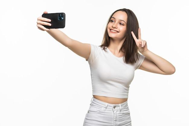Schöne junge frau macht selfie-foto mit smartphone