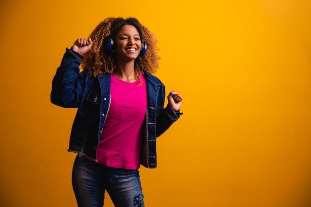 Schöne junge frau mit afro-haar, die mit ihrem kopfhörer musik hört und auf einem gelben hintergrund tanzt.