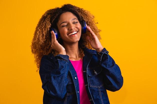 Schöne junge frau mit afrohaar, das musik mit dem kopfhörerlächeln hört.