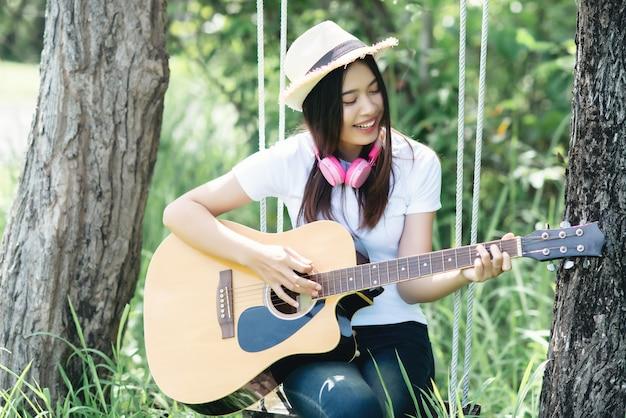 Schöne junge frau mit akustikgitarre an der natur